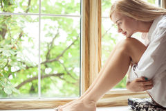 美丽的少妇在窗口附近休息 库存图片
