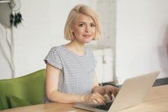 美丽的少妇在膝上型计算机前面坐 在她旁边的电话 免版税库存图片