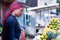 美丽的少妇在街道的水果市场上 库存照片