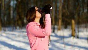 美丽的少妇在跑步以后喝茶在冬天森林里 影视素材