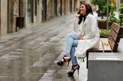 美丽的少妇在都市背景中谈话在电话 免版税图库摄影