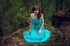 美丽的少妇坐一个岩石在森林 免版税库存照片