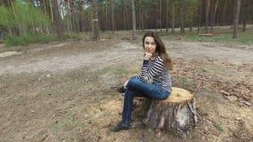 美丽的少妇坐一个树桩在夏天杉木公园 股票视频
