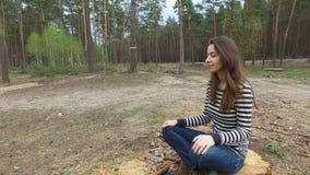 美丽的少妇坐一个树桩在夏天杉木公园 影视素材