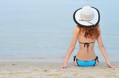 美丽的少妇坐一个沙滩,背面图,空间fo 免版税库存照片