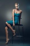 美丽的少妇坐一把椅子在演播室  库存图片
