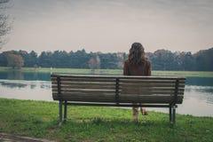 美丽的少妇坐一条长凳在城市公园 免版税库存图片