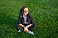 美丽的少妇坐室外的绿草 免版税库存照片