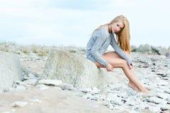 美丽的少妇坐岩石 免版税库存照片