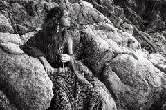 美丽的少妇坐石头户外 免版税库存照片