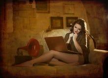 美丽的少妇坐研究膝上型计算机的床有一台红色留声机在她附近,在闺房风景。可爱的浅黑肤色的男人 免版税库存图片