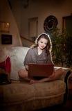 美丽的少妇坐研究膝上型计算机的沙发有一台红色留声机在她附近,在闺房风景 可爱的浅黑肤色的男人 库存图片