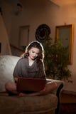 美丽的少妇坐研究膝上型计算机的沙发,在闺房风景 有长的头发和长的腿的可爱的深色的女孩 库存照片