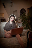 美丽的少妇坐研究膝上型计算机的沙发,在闺房风景 有长的头发和长的腿的可爱的深色的女孩 库存图片