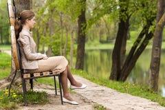 美丽的少妇坐长凳在朝前看的公园 免版税库存图片