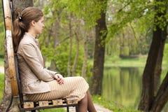美丽的少妇坐长凳在朝前看的公园 库存照片