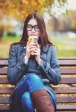 美丽的少妇坐长凳饮用的咖啡或热的茶在春天享用在公园的秋天外套室外 免版税库存图片