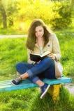 美丽的少妇女孩在春天的读一本书 图库摄影