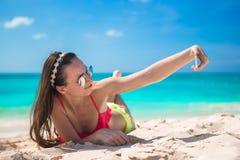 美丽的少妇拍照片的热带海滩的 免版税库存照片