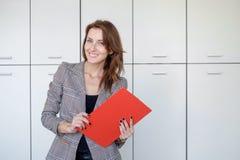 美丽的少妇拿着一个文件夹,看照相机并且微笑着,当站立在办公室时 免版税库存照片