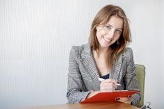 美丽的少妇拿着一个文件夹,看照相机并且微笑着,当站立在办公室时 免版税库存图片