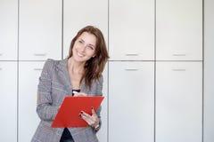 美丽的少妇拿着一个文件夹,看照相机并且微笑着,当站立在办公室时 库存照片