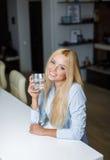 美丽的少妇拿着一块玻璃用水 库存照片