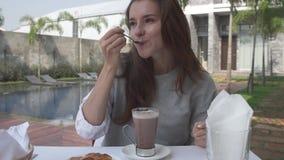 美丽的少妇搅动恶在早晨早餐期间在豪华别墅的水池附近 喝热巧克力的女性 影视素材