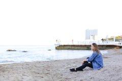 美丽的少妇放松坐海滩并且享受图o 免版税库存图片