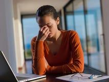 美丽的少妇放松并且研究膝上型计算机 免版税库存图片