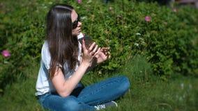 美丽的少妇是叫和谈话在坐在公园的手机 股票视频