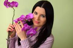 美丽的少妇有嫉妒和一朵桃红色兰花的浅黑肤色的男人 免版税库存照片