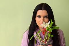美丽的少妇有嫉妒和一朵白色兰花的浅黑肤色的男人 免版税库存图片