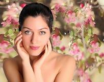 美丽的少妇有春天花背景 免版税库存照片