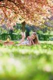美丽的少妇有野餐在开花的春天公园 库存图片