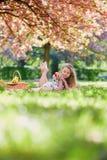 美丽的少妇有野餐在开花的春天公园 库存照片