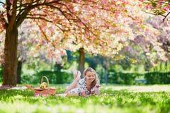 美丽的少妇有野餐在开花的春天公园 免版税图库摄影
