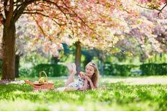 美丽的少妇有野餐在开花的春天公园 免版税库存图片