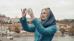 美丽的少妇游人在布拉格,做Selfie或拍与她的手机的照片,旅行的概念 库存图片