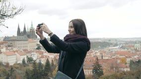 美丽的少妇游人在布拉格,做Selfie或拍与她的手机的照片,旅行的概念 免版税库存照片