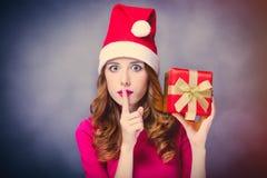 美丽的少妇照片在圣诞老人帽子有逗人喜爱的礼物的 库存照片