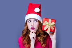 美丽的少妇照片在圣诞老人帽子有逗人喜爱的礼物的 图库摄影