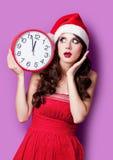 美丽的少妇照片有时钟的在圣诞老人帽子 免版税库存图片
