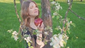 美丽的少妇用一个苹果在她的手上反对苹果树的背景 妇女吃一个苹果 庭院 影视素材
