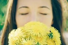 美丽的少妇用黄色蒲公英 库存图片