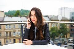 美丽的少妇画象咖啡店大阳台的,放松使用巧妙的电话,电话交谈户外 时尚fe 库存照片