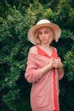 美丽的少妇画象宽海滩帽子的,反对夏天绿色公园背景  图库摄影