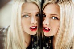 美丽的少妇白肤金发的女孩和她的反射画象在镜子 库存照片