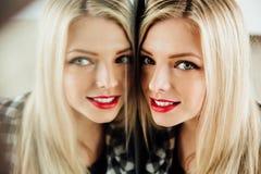 美丽的少妇白肤金发的女孩和她的反射画象在镜子 图库摄影