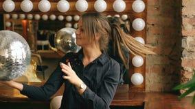 美丽的少妇的慢动作有摆在和微笑在演播室的迪斯科球的户内 影视素材
